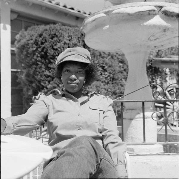 Poet Rita Dove wears a hat and sits by a fountain outside the Poetry Center.