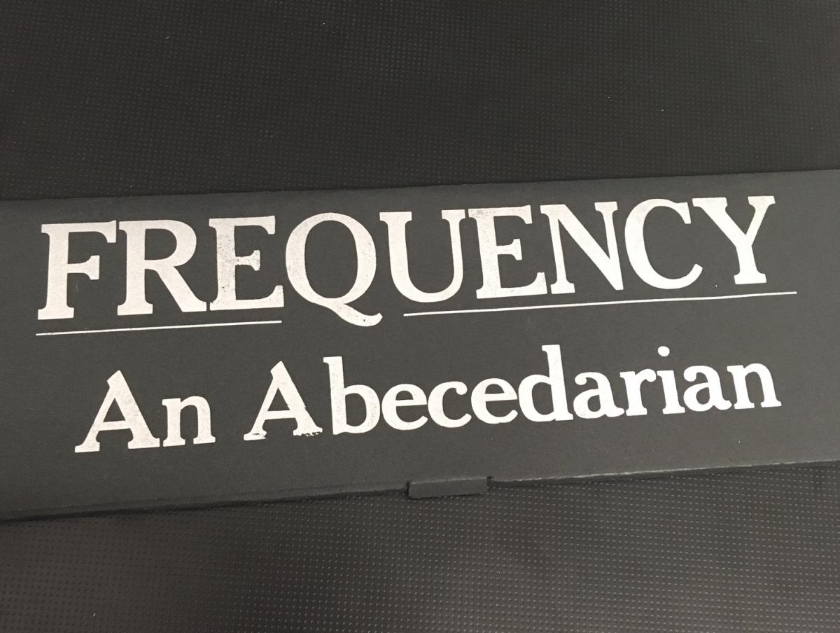 """Photo of """"Frequency: An Abecedarian,"""" letterpress silver letters on a black paper box"""