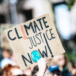 """A pale hand holds a sign that says, """"Climate justice now."""" Photo by Markus Spiske."""